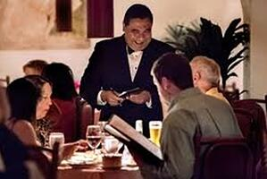 A server at a fine dining restaurant helping customers choose a wine